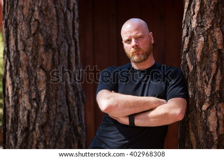Bald man with a beard and crossed arms