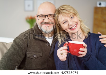 Bald man with glasses seated next to wife holding red coffee mug on couch in their living room - stock photo