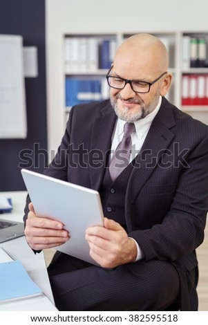 Bald middle-aged businessman wearing glasses and a stylish suit sitting in the office reading on his handheld tablet-pc with a smile - stock photo