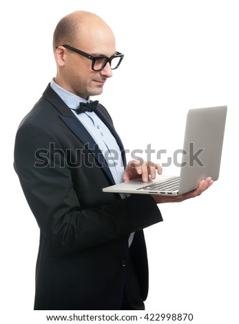 Bald stylish man in elegant black suit and glasses with laptop. Isolated on white