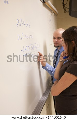 Bald teacher helping female student with a math problem on a whiteboard. - stock photo