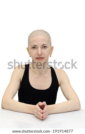 Bald woman in black sleeveless shirt, sitting relaxed at a table, palms joined. Isolated with clipping path.