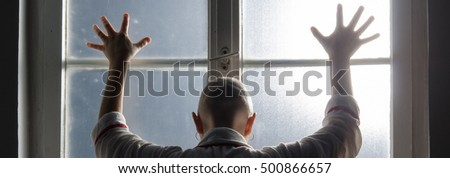 Bald woman suffering from cancer leaning on the hospital window.