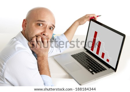 bald worried business man biting his fingernails with anxiety watching sales and finance collapse at his computer graphic  - stock photo