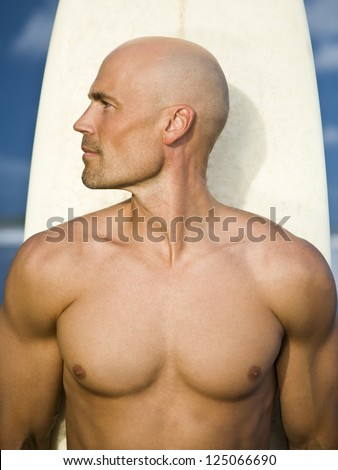 Bald young man holding a surfboard - stock photo