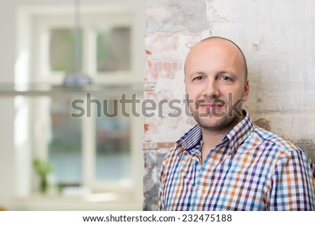 Balding middle-aged man in a checked shirt standing against a painted brick wall looking at the camera with a friendly smile, with copyspace - stock photo
