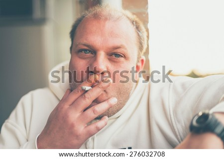 Balding middle-aged man sitting smoking indoors puffing on his cigarette with obvious enjoyment, close up head and shoulders portrait
