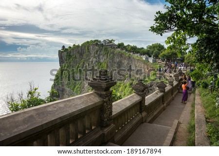 BALI - APRIL 12, 2014: Tourists climb the steps up the cliff to reach an ancient temple at the top in Uluwatu, Bali Island. The famous Balinese dance 'kecak' performed here is a tourist attraction.