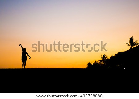 Bali in Indonesia dancing girl silhouette at Sanur Beach sunset