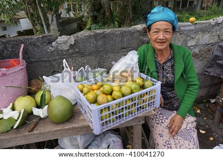 Bali Indonesia Apr 4, 2016 : Unidentifiied Balinese woman selling navel orange at roadside near Batur. The place located in central Bali is famous for its active volcano Mount and Lake Batur.