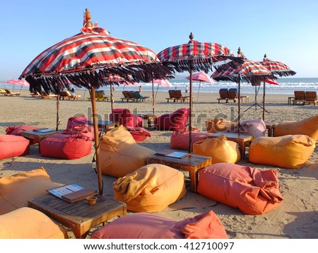 BALI, INDONESIA - APRIL 28, 2016: Bean cushions, umbrellas and sun beds on beach the beach, Seminyak, Bali, Indonesia.