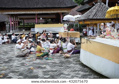 Bali, Indonesia - April 8, 2016: Local Balinese praying at holy spring water temple Pura Ulun Danu Bratan during the religious ceremony in Bali, Indonesia.