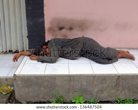 BALI, INDONESIA - APRIL 10: Unidentified homeless man sleeping on sidewalk on April 10, 2013, in Bali, Indonesia. Bali one of the wealthiest places in Indonesia still has over 25,000 homeless people. - stock photo