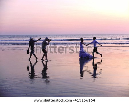 BALI, INDONESIA - APRIL 28, 2016: Wedding couple running on the beach for pre wedding photo shoot in Bali, Indonesia.