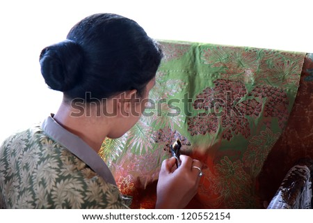 BALI, INDONESIA - AUGUST 26, 2011: An unidentified Balinese woman applies dye on a piece of batik, on August 26, 2011 in Bali, Indonesia. Batik-making is an important part of Indonesian culture. - stock photo