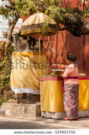 BALI, INDONESIA - AUGUST 27, 2015: Balinese woman offers flowers and food to a hindu god in Ubud, Bali, Indonesia on August 27th, 2015. - stock photo