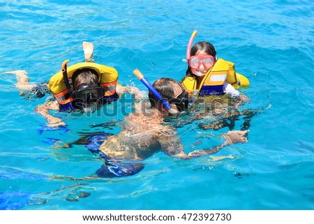 BALI, INDONESIA - AUGUST 10, 2016 : Father and daughters  enjoy snorkelling in a tropical sea at Nusa, Bali, Indonesia