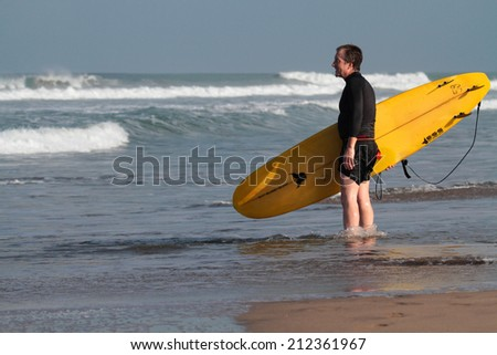 BALI, INDONESIA, AUGUST 8, 2014 : Surfer at Kuta Beach. Kuta is known internationally for its long sandy beach, varied accommodations, many restaurants and bars, and many renowned surfers.