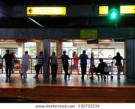 BALI, INDONESIA - FEB 18: People waiting for passengers at an airport, February 18, 2013, Bali, Indonesia. This tourist destination received 15 million passengers in 2012, up from 6 million in 2010. - stock photo