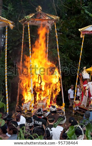 BALI, INDONESIA, JULY 14: Funeral pyres in the form of a bull are set on fire during a cremation ceremony in Penestanan, Bali on July 14th 2010. - stock photo