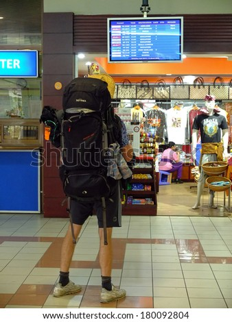 BALI, INDONESIA - JULY 6, 2013: Man looking at flight schedules on a screen at Bali international airport. - stock photo