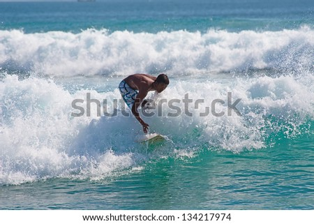 BALI, INDONESIA - JULY 27: Unidentified young man surfing the waves on July 27, 2010. Dreamland beach, Bali, Indonesia. The Dreamland is one of the most popular surfing areas of Bali. - stock photo