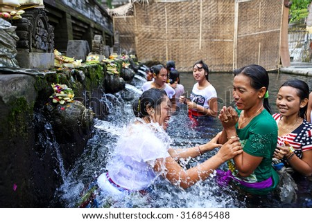 BALI, INDONESIA - JUN 19 : Unidentified Balinese people come to the sacred springs water temple of Tirta Empul on June 19, 2015 in Bali, Indonesia. It is a to pray and cleanse of Balinese - stock photo