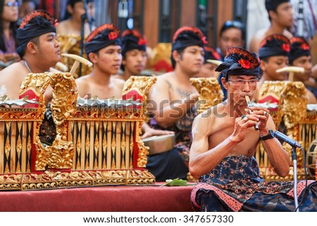 BALI, INDONESIA - JUNE 21, 2015: Old musician man of traditional Gamelan orchestra dressed in Balinese style male costume playing ethnic music on bamboo flute Suling at Art and Culture Festival. - stock photo