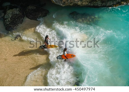 BALI, INDONESIA - 25 JUNE 2016: Unidentified surfers entering sea at Blue Uluwatu point.