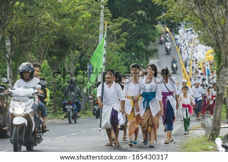 BALI, INDONESIA - MARCH 30: Balinese villagers participating in traditional religious Hindu procession before Ogoh-ogoh parade and Nyepi day (Balinese New Year) in Canggu, Bali on March 30, 2014