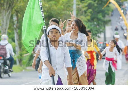 BALI, INDONESIA - MARCH 30: Balinese villagers participating in traditional religious Hindu procession before Ogoh-ogoh parade and Nyepi day (Balinese New Year) in Canggu, Bali on March 30, 2014 - stock photo
