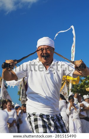 BALI, INDONESIA - MARCH 18: Face portrait of an unidentified man in trance, during traditional ritual fighting dance on Melasti - religious ceremony of Balinese people, Bali on 18 March, 2015 - stock photo