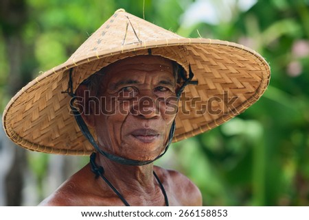 BALI, INDONESIA - MARCH 20: Portrait of unidentified old Balinese farmer with a wrinkled face in traditional straw wide-brimmed hat during harvesting crop in rice terraces in Bali on 20 March, 2015