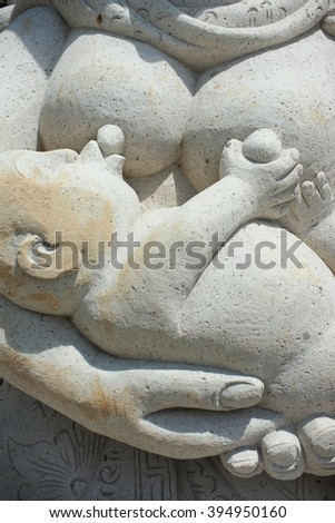 BALI, INDONESIA - March 23, 2016: The stone sculpture of a mother breast-feeding her young baby at Tirtha Empul Temple on March 23, 2016 in Tampaksiring, Bali, Indonesia.