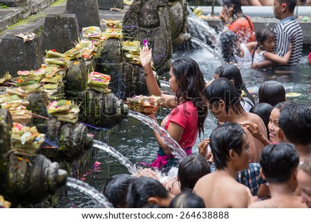 BALI, INDONESIA - MARCH 29, 2015 : Unidentified Balinese families come to the sacred springs water temple of Tirta Empul in Bali, Indonesia to pray and cleanse their soul - stock photo