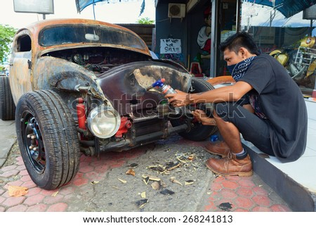 BALI, INDONESIA - MARCH 20: Young Balinese man cleans a body of old volkswagen beetle during the making and vintage custom hotrod car in the auto and moto repair shop in Bali island on 20 March, 2015