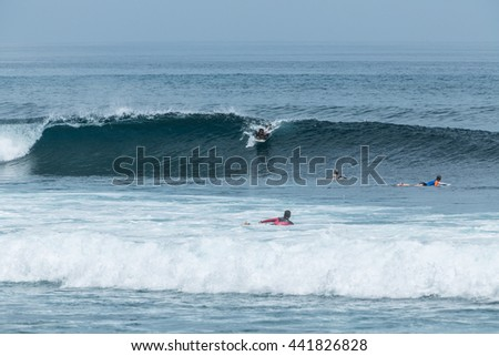 BALI, INDONESIA - MARCH 29, 2016: Young surfers in rough seas sail on Blue Ocean Wave on Balangan beach, Bali
