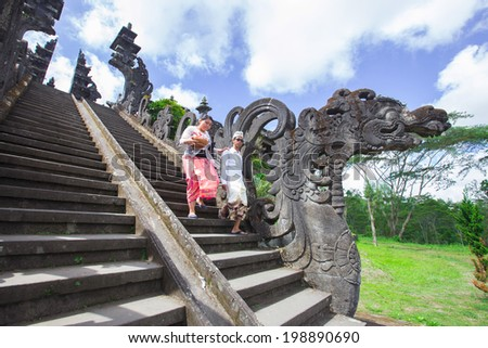 BALI, INDONESIA, May 30: Couple go down after praying in Besakih temple on May 30, 2014 in Bali, Indonesia. Besakih temple is one of the most famous hindu temple in Bali island - stock photo