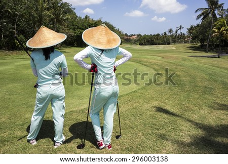 BALI, INDONESIA - NOV 8, 2012: Two caddies with straw hats on a golf course near Tabanan in Bali watch as their players hit on the 18th fairway. In Indonesia, caddies are always women. - stock photo