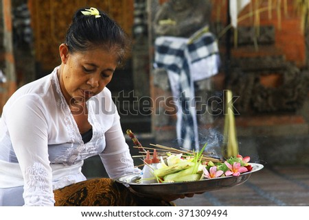 BALI, INDONESIA - November 24, 2015 - Asian woman with incense and offerings - stock photo