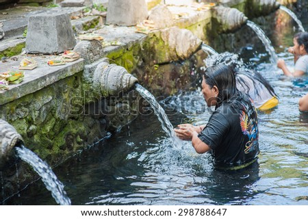 BALI, INDONESIA - NOVEMBER 3RD 2014 : Balinese people cleansing themselves in the Holy Spring at Tirtha Empul Bali, Indonesia.