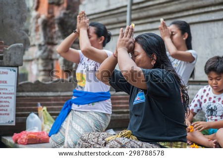 BALI, INDONESIA - NOVEMBER 3RD 2014 :  Balinese people pray before they cleanse themselves in Holy Spring at Tirtha Empul Bali, Indonesia. - stock photo