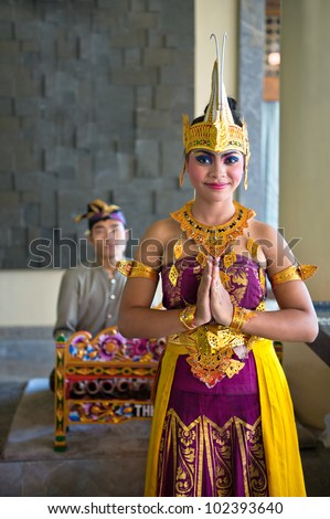 BALI, INDONESIA - NOVEMBER 15: young balinese female dancer in traditional dress  welcomes arriving tourists on November 15, 2011 on Bali,Indonesia. At 2010 Bali received 2.57 million foreign tourists - stock photo