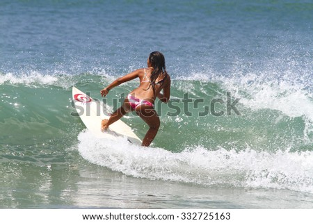 BALI,INDONESIA, OCTOBER 28, 2015; a surfer girl at Kuta beach at sunny day.