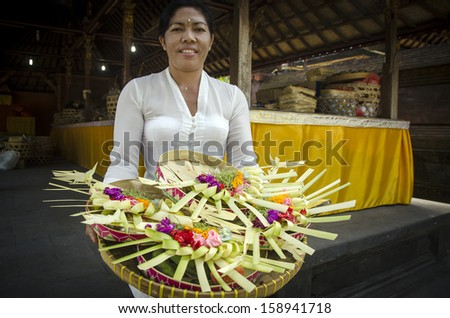 BALI, INDONESIA - OCTOBER 14, 2013: An unidentified Balinese woman displays Hindu temple decorations, on OCTOBER 14, 2013 in Bali, Indonesia. Hindu ceremonies are an important part of Bali's culture.  - stock photo