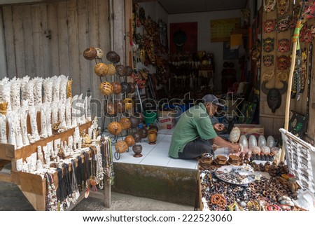 BALI, INDONESIA - SEPTEMBER 20, 2014: A trader waits for customers at his shop selling handicrafts and souvenir items made from natural resources from his village. - stock photo