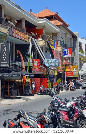 Bali, Indonesia - September 14, 2015: Colourful shops, resturants & scooters on the tiny main street in Seminyak. - stock photo