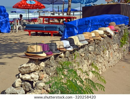 Bali, Indonesia - September 14, 2015: Entrance to Legian Beach including bar, trees and sun Umbrellas and Hats for sale or rent. - stock photo