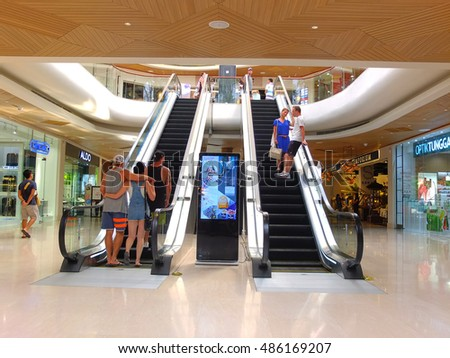 BALI, INDONESIA - SEPTEMBER 18, 2016: Escalators in modern Bali Village Mall with foreign tourists, Seminyak, Bali, Indonesia.