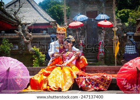BALI, INDONESIA - SEPTEMBER 22: Indonesian just married couple dressed in traditional balinese clothing posing infront of the temple in Bali, Indonesia on September 22, 2014 - stock photo